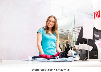 Salesperson Standing At Cash Register