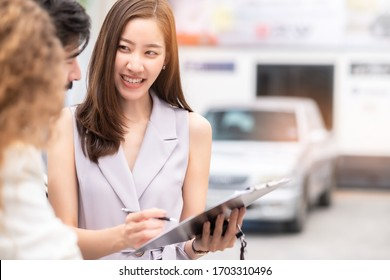 Salesperson working at car dealership.Young Asian woman consultant and couple buyers signing contract for new car in auto show. Concept for car rental or sale.
