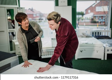 A saleswoman is assisting a young man as he shops for a new matress. She is talking to him while he tests a display.