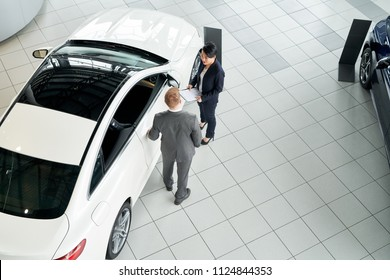 Saleswoman and customer standing near the new car and communicating