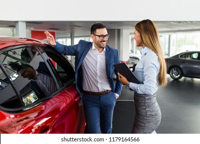 Saleswoman at the dealership showroom talking with customer and helping him to choose a new car for himself.