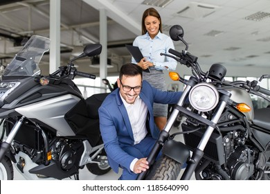 Saleswoman at the dealership showroom talking with customer and helping him to choose a new motorcycle for himself.