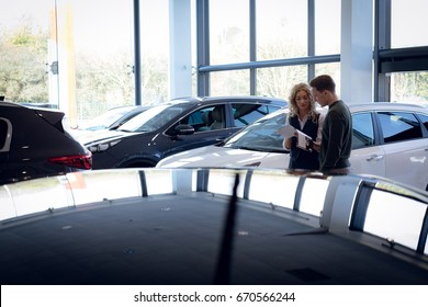 Saleswoman discussing over brochure with customer while standing by cars in showroom