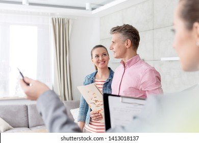 Saleswoman gesturing to smiling couple standing with brochure at home