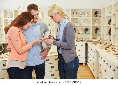 Saleswoman giving consultation to happy couple in a jewelry store