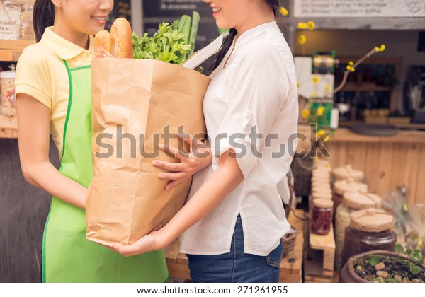 Saleswoman helping customer with shopping bag at the grocery store