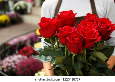Saleswoman holding bouquet of beautiful roses in shop