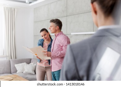 Saleswoman looking at couple standing with document at home