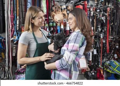 Saleswoman Looking At Female Customer Carrying French Bulldog