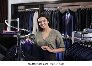 Saleswoman near rack with suit jackets in boutique