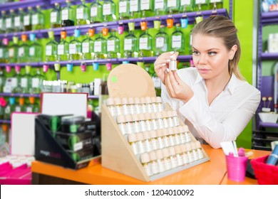 saleswoman offering new fragrance in perfume shop