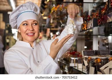 saleswoman posing with fine ganaches and praline chocolates