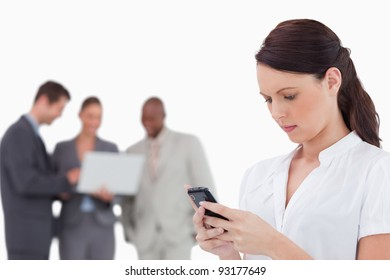 Saleswoman reading text message with colleagues behind her against a white background