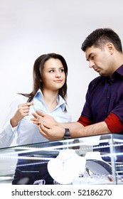 The saleswoman in shop helps to choose a jewel