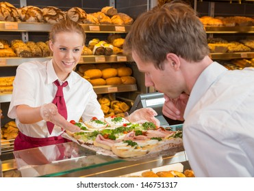 Saleswoman or shopkeeper in bakery presenting tablet with sandwiches to customer
