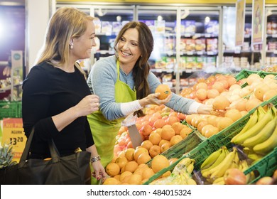 Saleswoman Showing Fresh Oranges To Female Customer