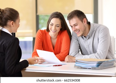Saleswoman talking with a couple of happy customers sitting in a desktop at office