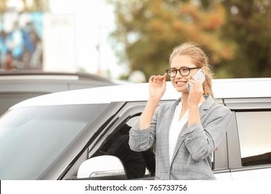 Saleswoman talking on phone near new car outdoors