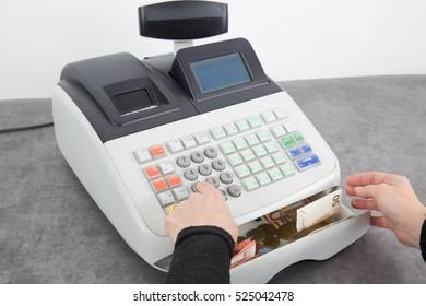 Saleswoman using cash desk at boutique counter