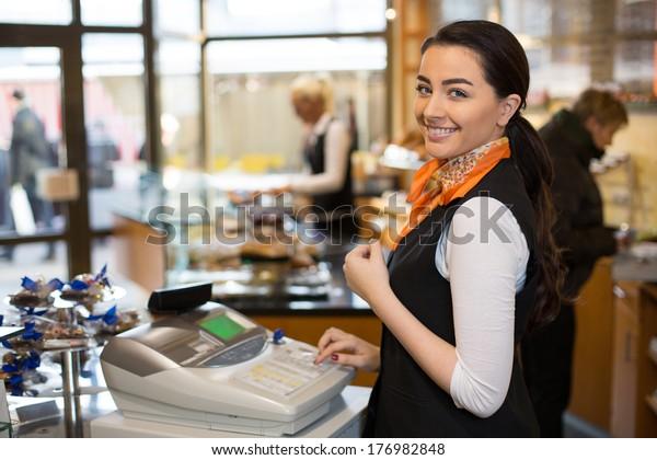 Verkäuferin, die in der Kasse arbeitet