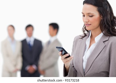 Saleswoman writing text message with colleagues behind her against a white background