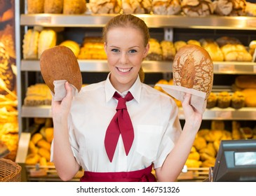 Salewoman or shopkeeper in a bakery presenting two different types of bread to customer