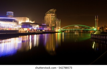 Salford quays and MediaCity at night, Lowry gallery and theatre, millennium lift bridge, blurred reflection in the water, shining lights, Greater Manchester city, United Kingdom UK