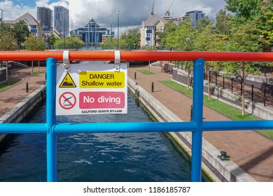Salford Quays, UK - August 24,2018: sign warning of no diving and shallow water over a canal in Salford Quas, Manchester, UK