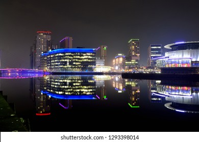 SALFORD / UK - January 2019: Salford Quays at night. Media City is home to production studios of both the BBC and ITV as well as a variety of bars, restaurants and the Lowry Theatre.