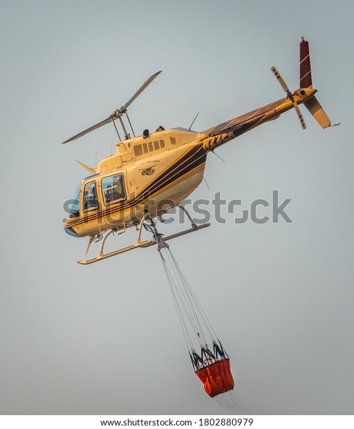 """Salinas, California - August 17, 2020:  A Cal Fire helicopter pilot carries a bucket of water to douse the """"River Fire"""" in the hills Monterey County of the central coast."""