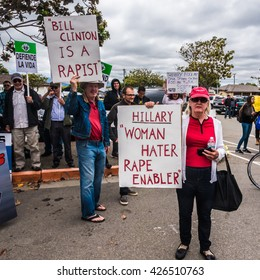 "Salinas, California - May 25, 2016: Protesters at the Hartnell College Hillary Clinton rally hold signs reading ""Bill Clinton is a Rapist"" and ""Hillary Woman Hater Rape Enabler"""