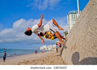 SALINAS, ECUADOR - SEPTEMBER 10: Unidentified Children practicing Parkour that developed out of military obstacle in the beach of Salinas, Ecuador on September 10, 2011 in Salinas, Equador