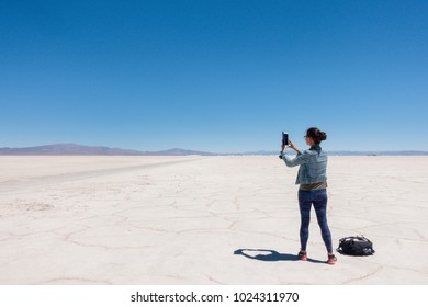 SALINAS GRANDES, JUJUY, ARGENTINA - OCTOBER 20, 2017: FEMALE VISITOR TAKES PHOTOS OF THE SALT FLATS IN NORTHERN ARGENTINA.