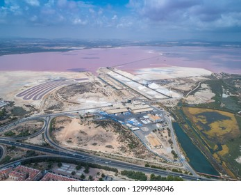 Salinas of Torrevieja. Aerial wide view on rose salty lake and small bungalows and highway to Cartagena