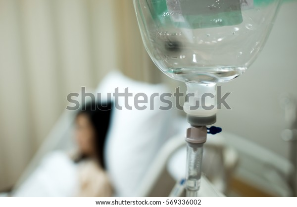 Saline IV drip bottle provided to the patient girl on the background