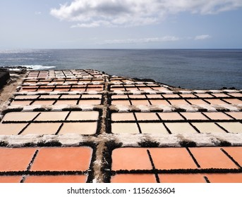 Salines, salt production in Fuencaliente on the Canary Island of La Palma. In the foreground the different maturity of the salt are divided into parcels, from pink to snow white, behind the blue Sea.