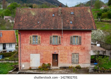 Salins-les-Bains - April 30 2008 - The First Local Bank of the Crédit Agricole, which has been housed in this pink house since 1888. The small village can be seen in the background.