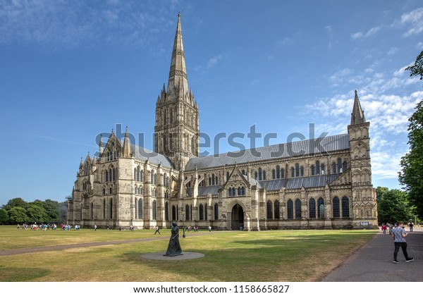"Salisbury Cathedral on a summer afternoon as seen from the North. In the foreground is the Statue of the ""Walking Madonna"" by Elizabeth Frink"