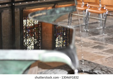 Salisbury, UK. January 31 2019. Salisbury Cathedral's famous flowing font with some of its historic stain glass windows reflected in the water