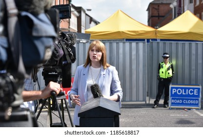Salisbury, UK - July 6, 2018: A news reporter broadcasts live on TV as police cordon off a hostel as investigations continue after local residents fall ill with nerve agent poisoning.