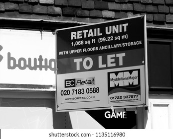 Salisbury, Wiltshire, England - July 10, 2018: monochrome retail unit to let estate agent advertising sign over vacant shop premises