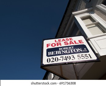 Salisbury, Wiltshire, England - July 25, 2017: Estate agent advertising sign, retail unit lease for sale, over vacant shop premises