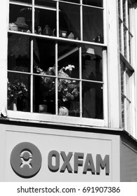 Salisbury, Wiltshire, England - July 25, 2017: Monochrome Oxfam charity shop sign over retail store, finding solutions to poverty and injustice around the world, founded in 1942