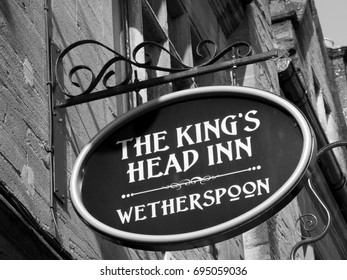 Salisbury, Wiltshire, England - July 25, 2017: Monochrome JD Wetherspoon The Kings Head Inn public house and hotel sign above premises, the site has been an inn since the fifteenth century