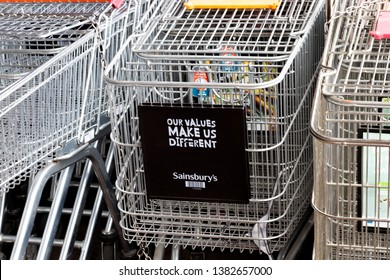 Salisbury, Wiltshire, England - March 30, 2019: shopping trollies stored outside Sainsburys supermarket with advertising on front