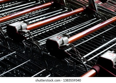 Salisbury, Wiltshire, England - March 30, 2019: shopping trollies stored outside Sainsburys supermarket entrance with coin operated security devices
