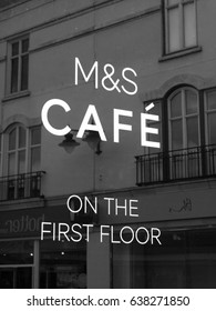 Salisbury, Wiltshire, England - May 5, 2017: Monochrome Marks and Spencer sign on shopfront window advertising in store cafe, company founded in 1884 by Michael Marks and Thomas Spencer