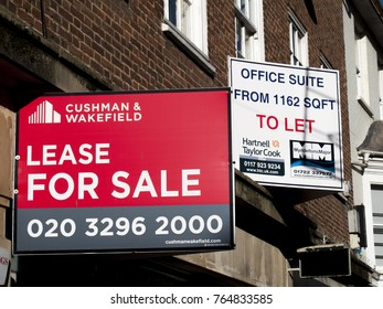 Salisbury, Wiltshire, England - November 28, 2017: Estate agent advertising signs, retail unit lease for sale over vacant shop premises and offices to let