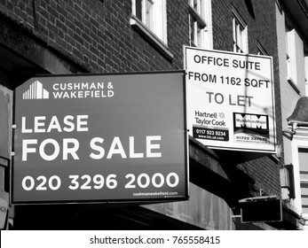Salisbury, Wiltshire, England - November 28, 2017: Monochrome estate agent advertising signs, retail unit lease for sale over vacant shop premises and offices to let