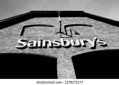 Salisbury, Wiltshire, England - October 7, 2018: monochrome Sainsburys supermarket sign over entrance, founded in 1869 by John James Sainsbury with a shop in Drury Lane London